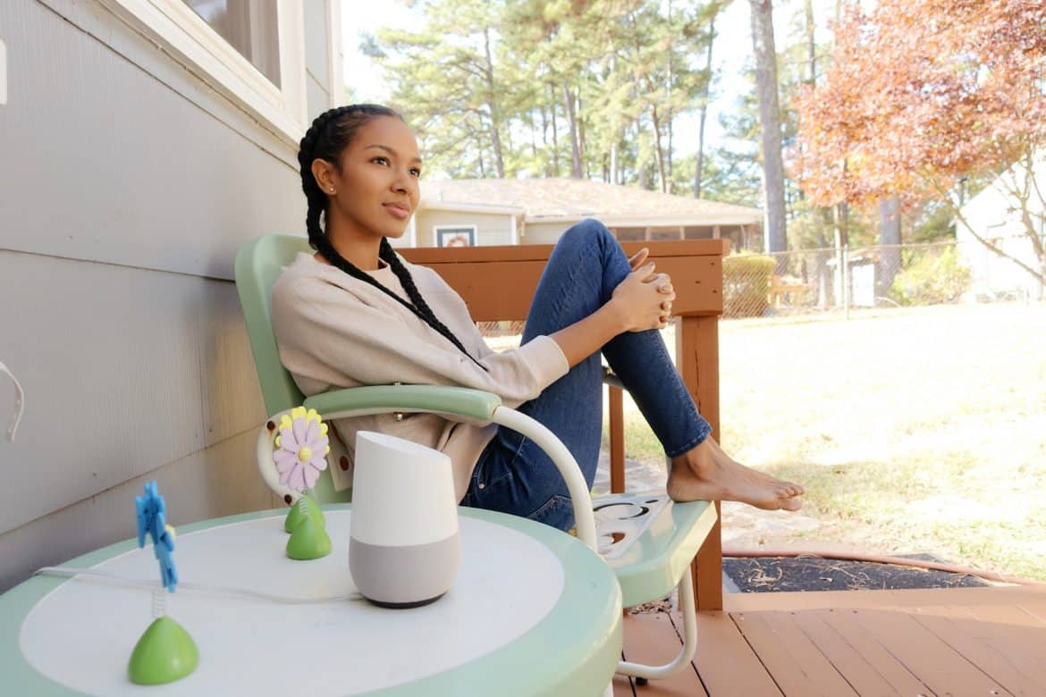 Girl On A Chair Next To Google Home