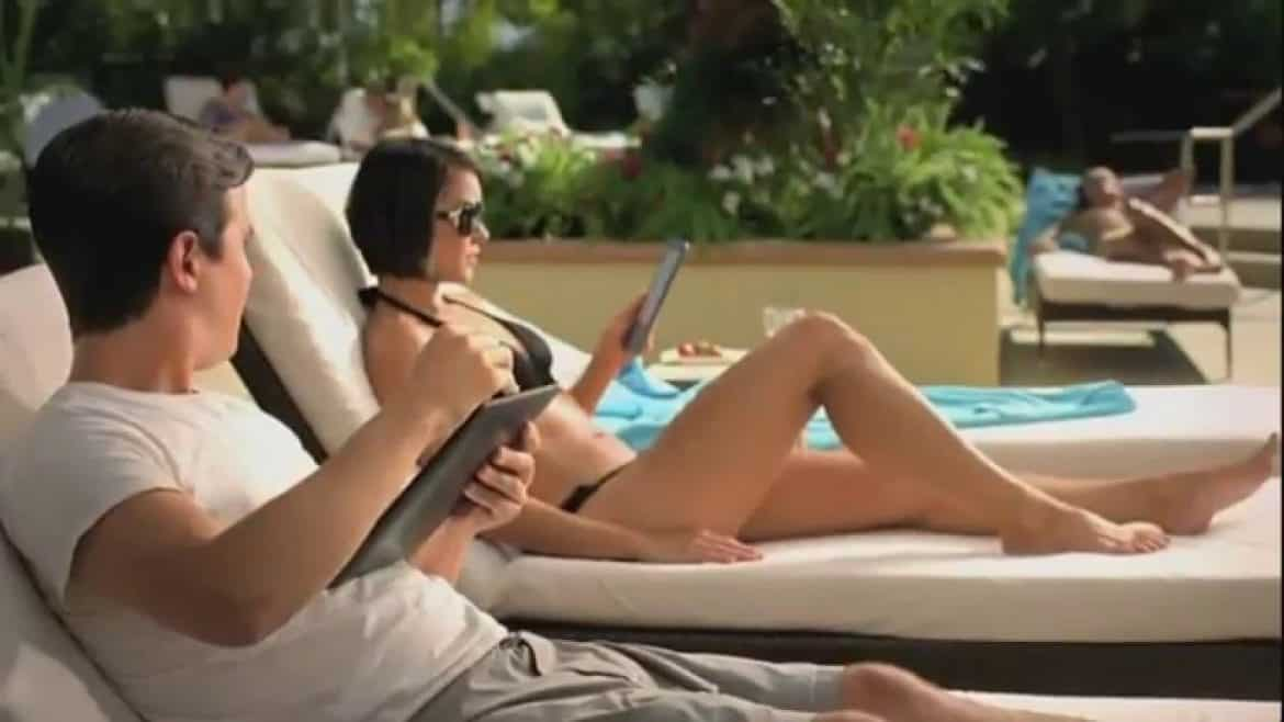 girl holding a e reader on sun bed