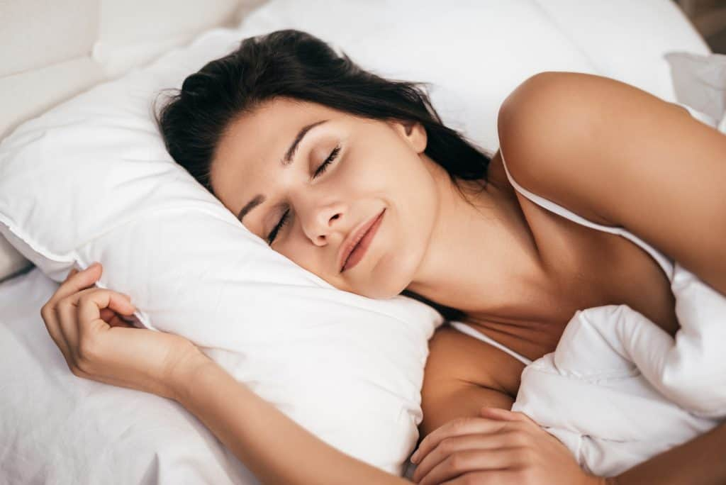 Sleeping at home. Beautiful young woman smiling during sleeping while lying in the bed at home