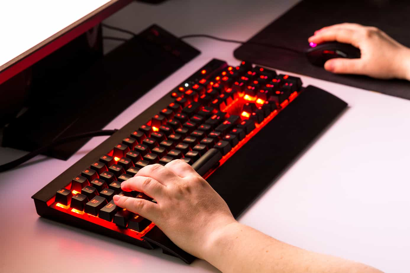 Female hands on keyboard playing computer game with gaming gear.