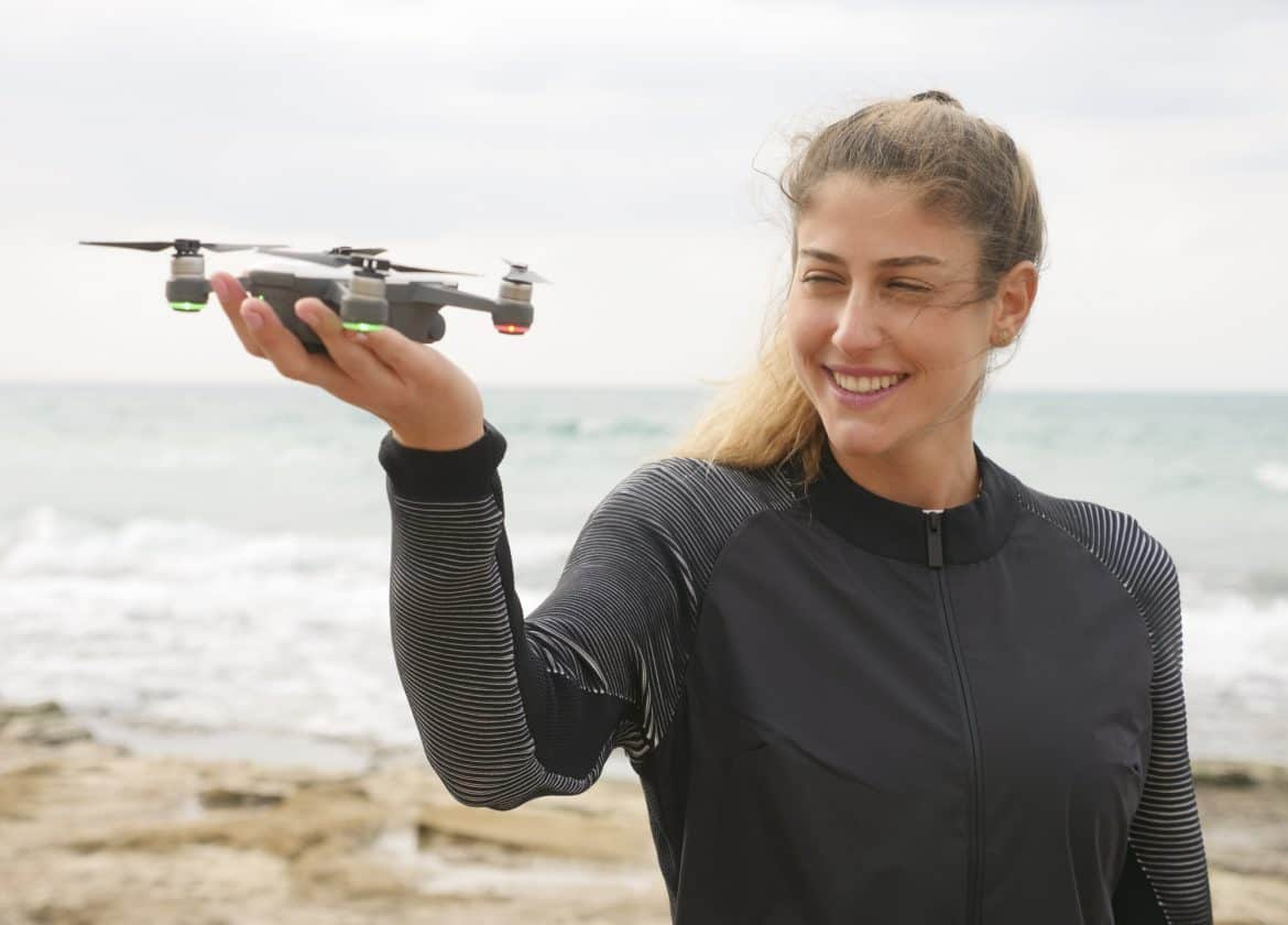 Young woman holding a selfie drone
