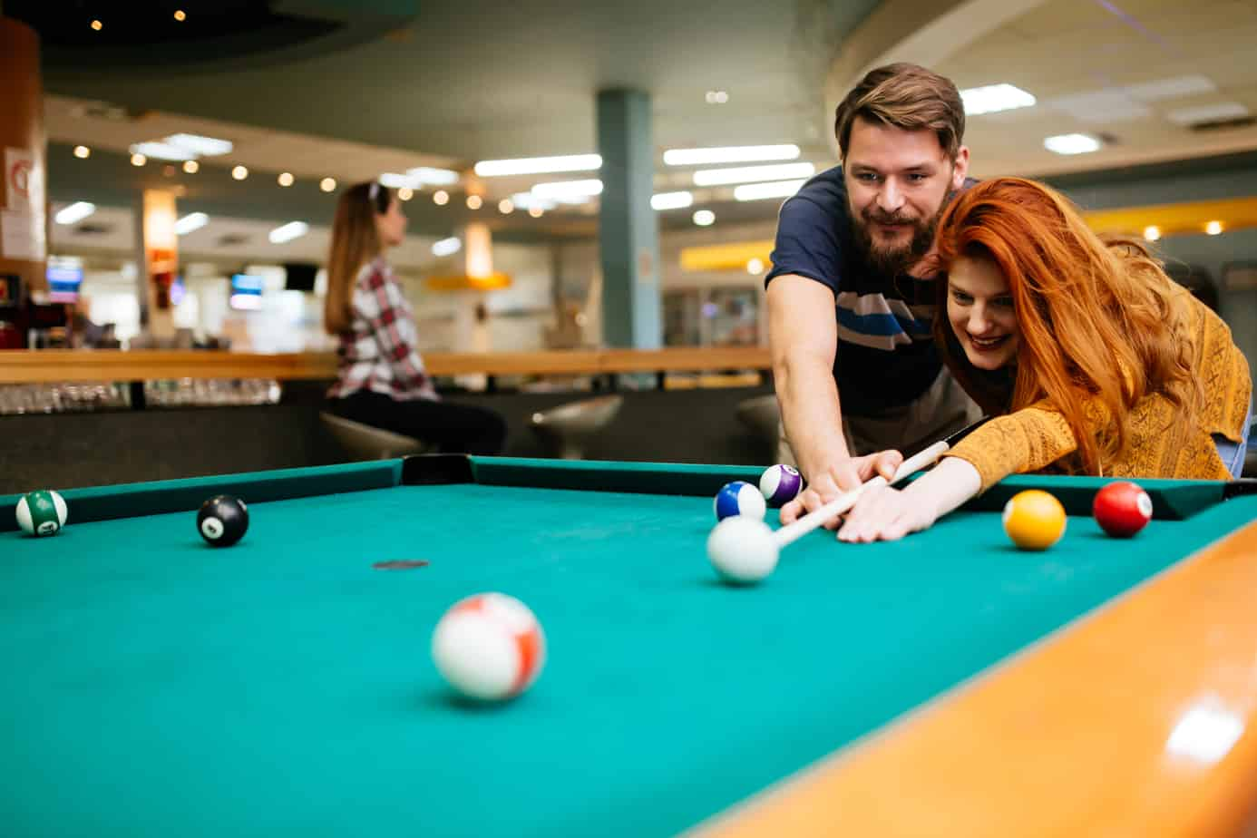 Couple playing billiards on pool table