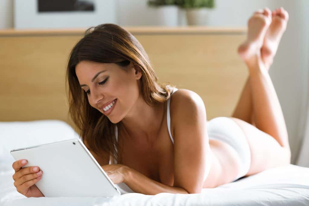 Pretty young woman looking her tablet while lying on the bed at