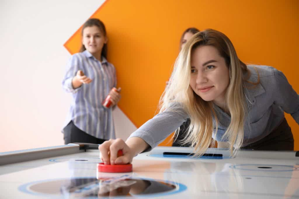 Young women playing air hockey indoors