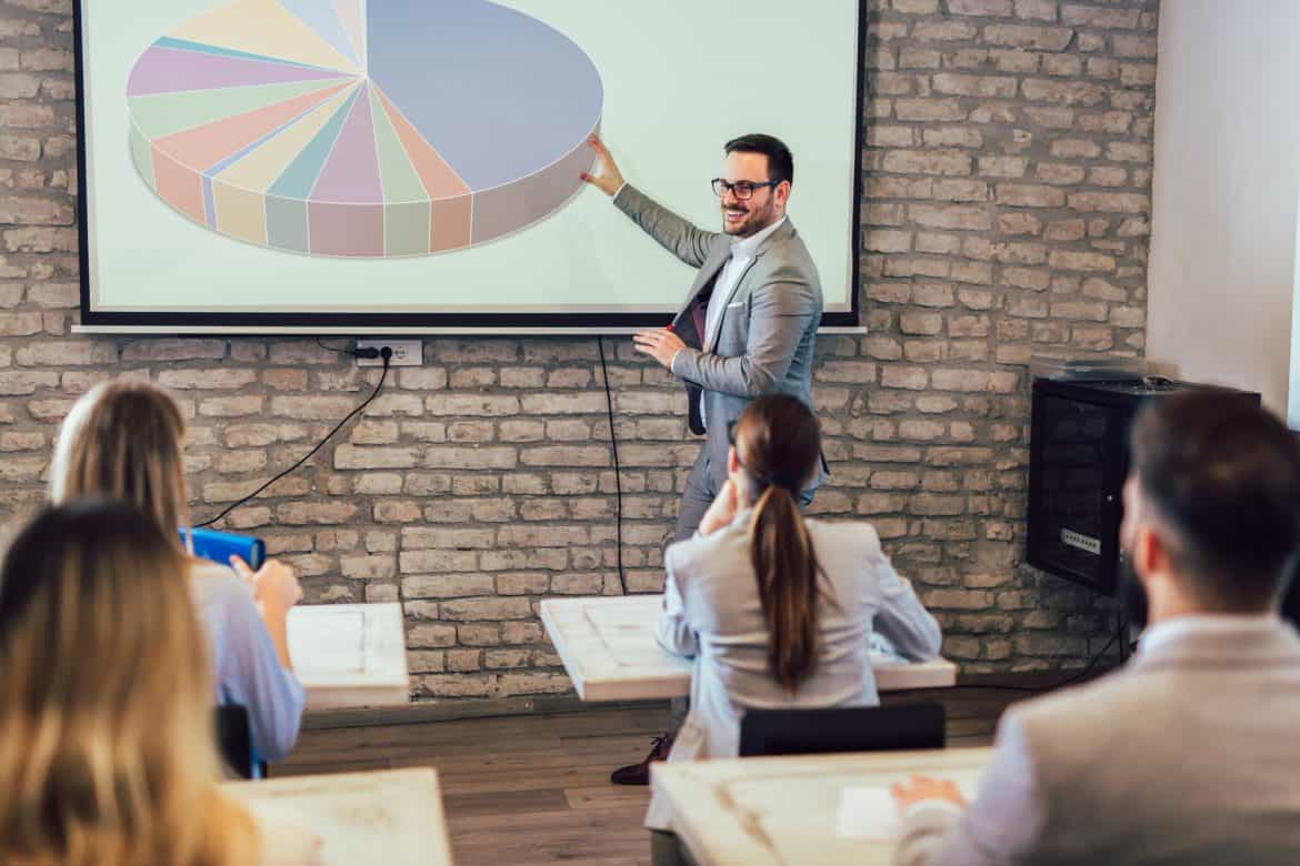 Confident speaker giving public presentation using projector in