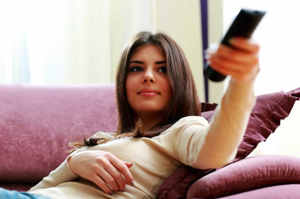 Young beautiful woman lying on the sofa with remote control at home