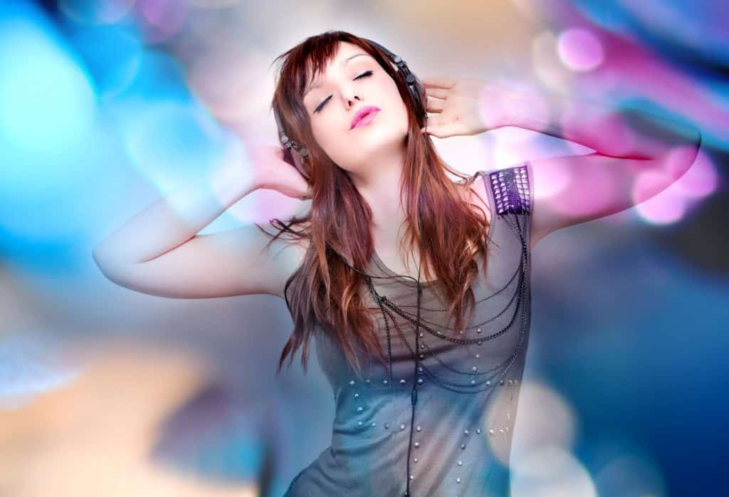 Beautiful young woman listening to music with headphones on background with stage lights