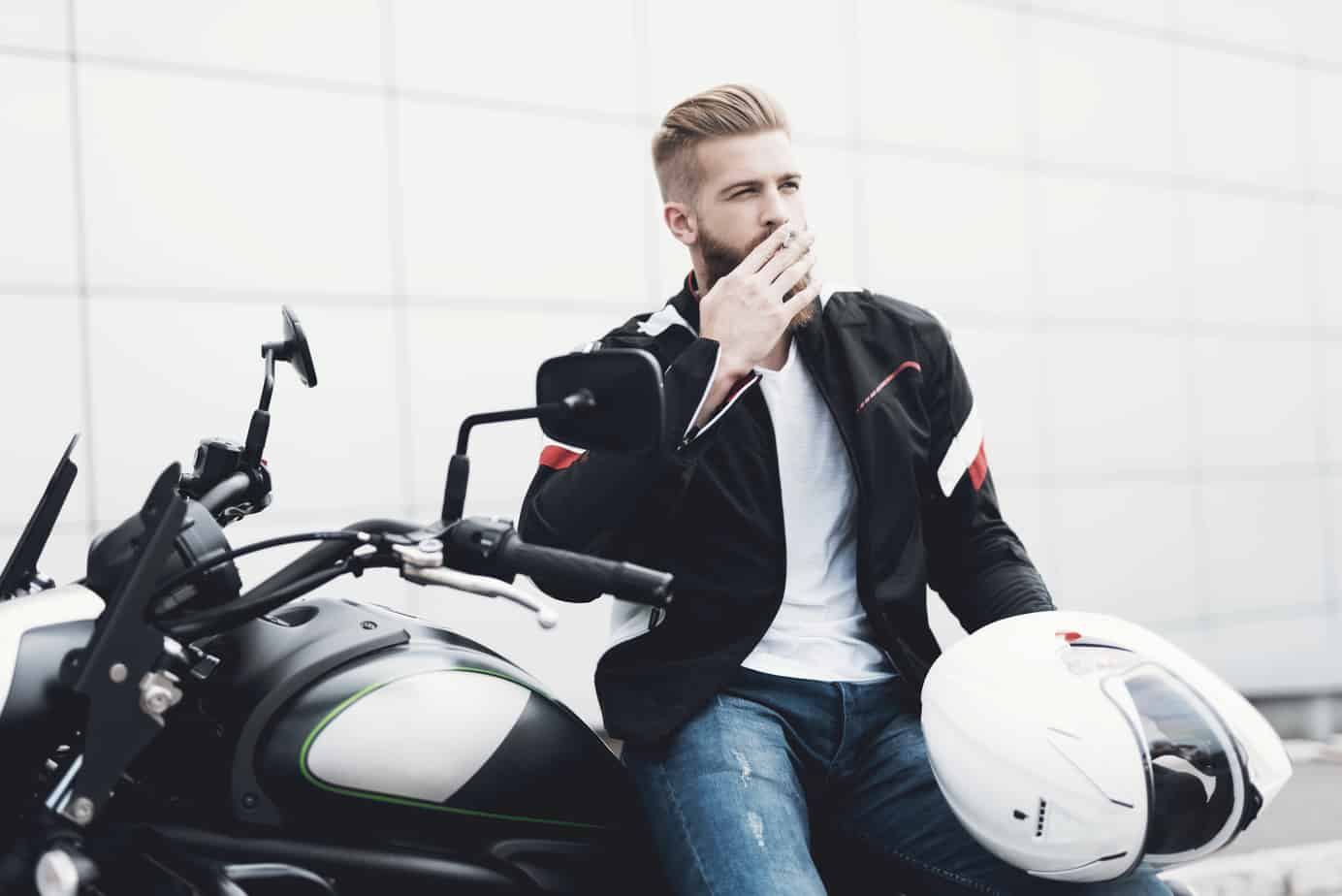 A young guy with a beard sits on his electric motorcycle.