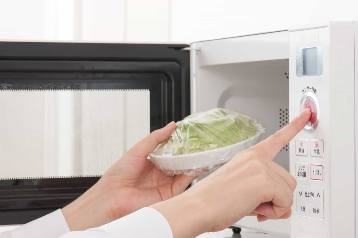 Woman Using Over The Range Microwave