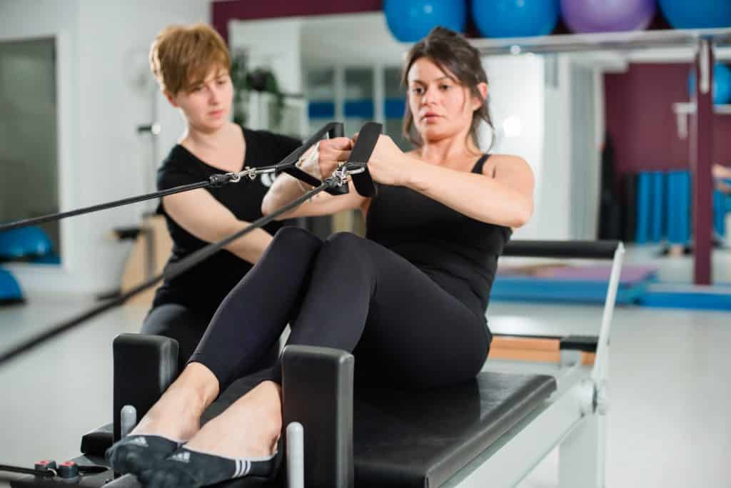 Young woman exercising on pilates device reformer with instructor at gym