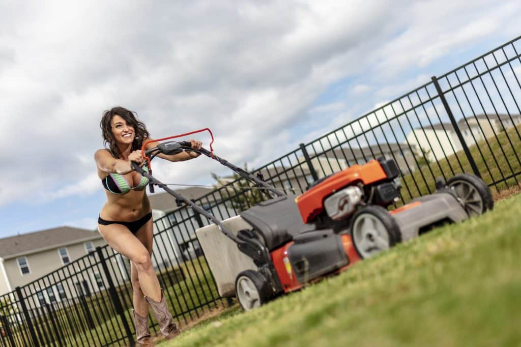 Brunette Cutting Grass With A Mower