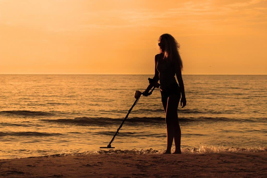 silhuete girl with metal detector on the beach on the sunset