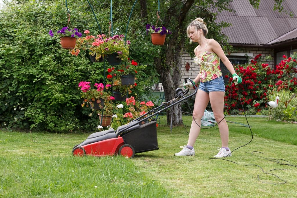 Woman with a corded mower