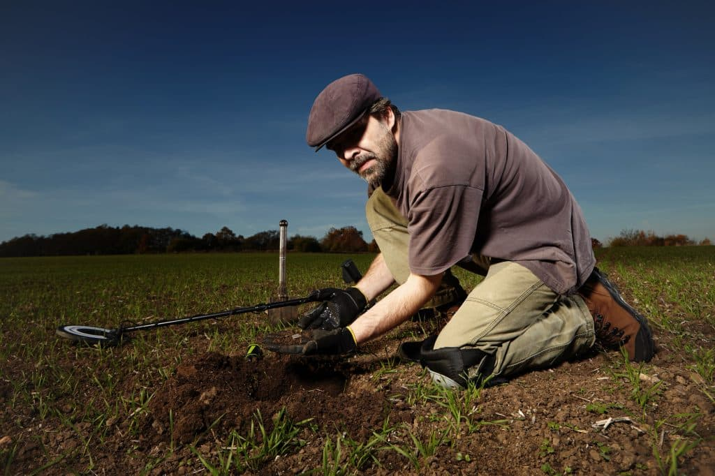 Amateur archeologist with metal detector in field