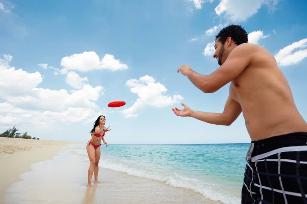 Playing Frisbee flying disc on beach