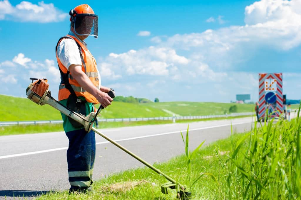 Road landscaper cutting grass using string lawn trimmer