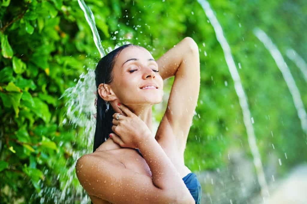 Woman having shower under tropical waterfall,