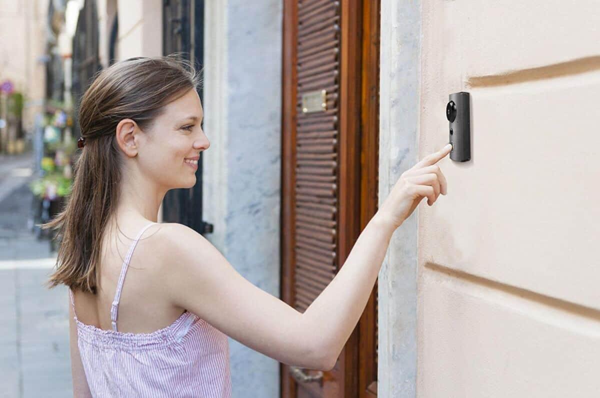 Woman pressing a smart doorbell