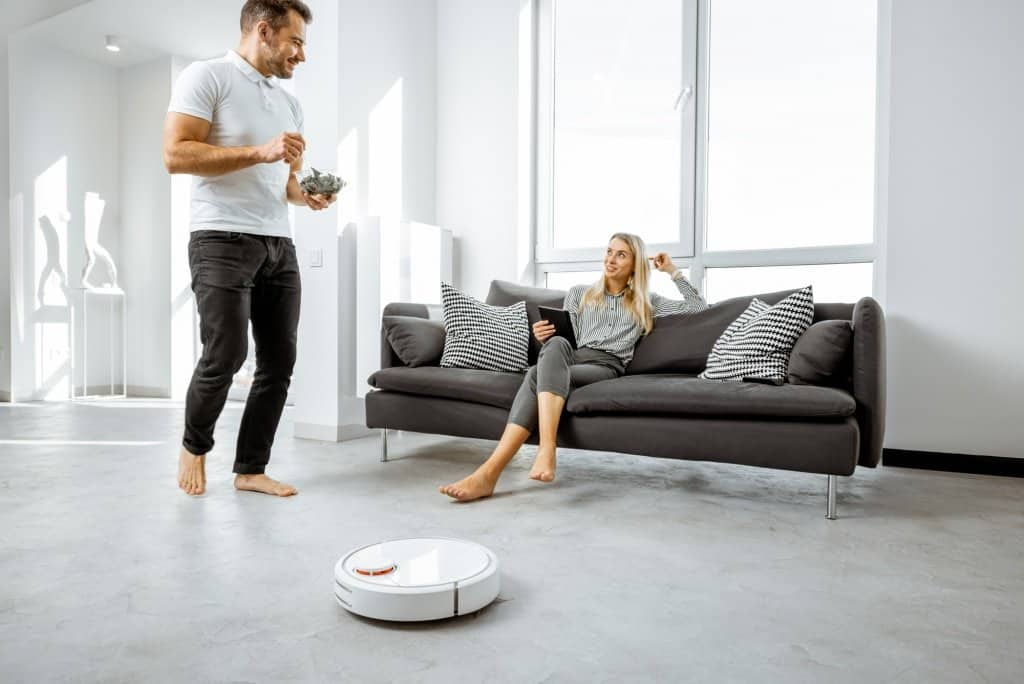 Couple on Sofa and robot vacuum on floor