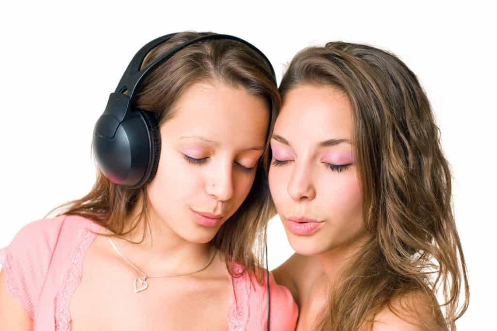 Girlfriends sharing music on same headphone