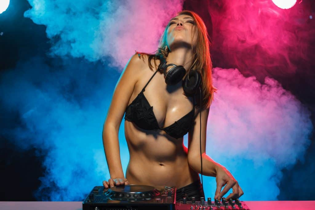 Excited DJ girl on decks on the party