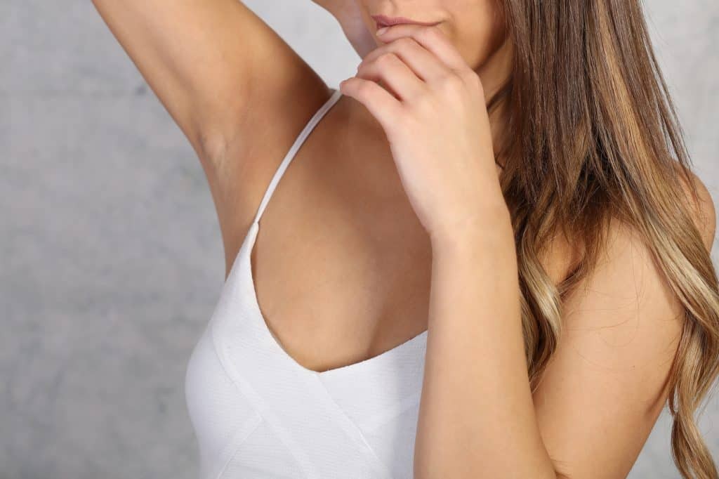 Armpit epilation, hair removal. Young woman showing clean underarms, depilation smooth clear skin