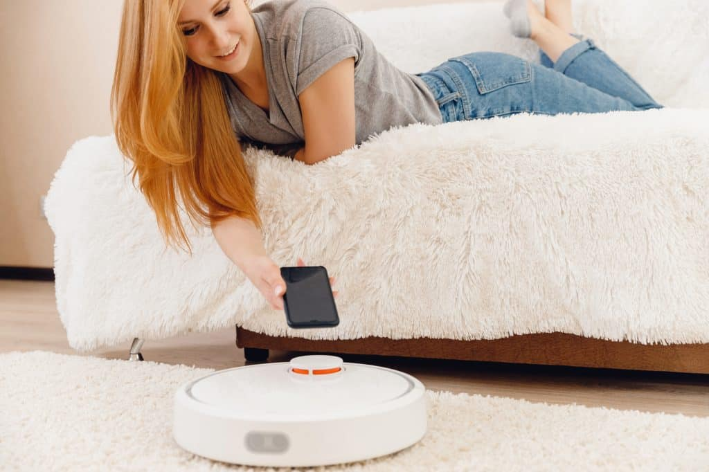 Young girl using automatic robot vacuum cleaner working on carpet. Controlling smart home functions with phone